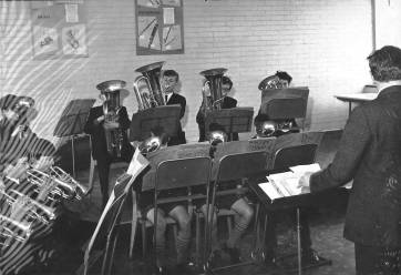 The Band in rehearsal under the baton of Peter Woodward, possibly in the School dining hall?